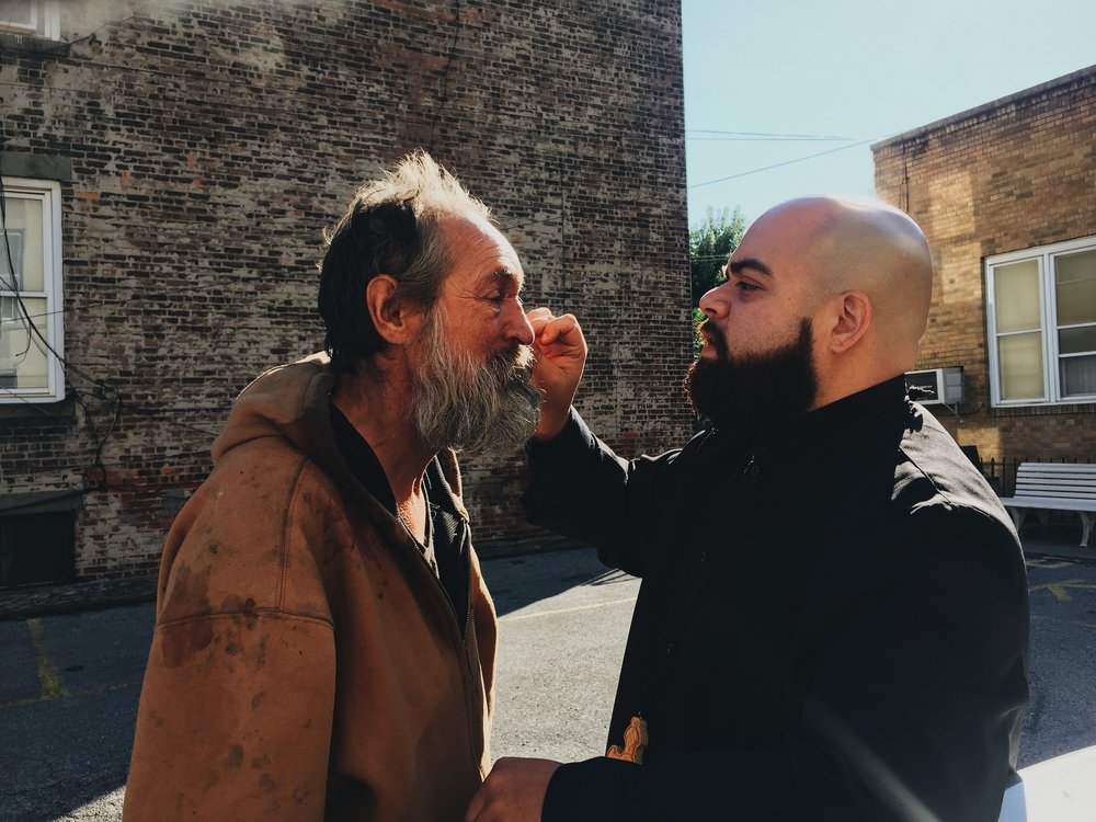 Father Mike Lopez helps Jerry Lewandowski, 54, clean the blood off his face in the parking lot of All Saints Church in Ridgewood, Queens.