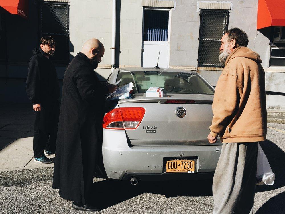 Arek Jasinski (left), 44, watches as Lopez sorts through the first aid kit he retrieved from his car as Lewandowski (right) watches.