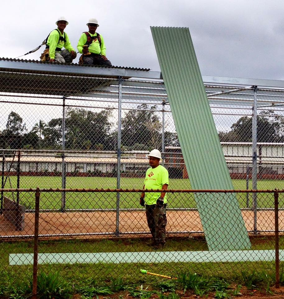 Foremen Victor, Lito & Romulo installing metal roofing panels over the batting cage.