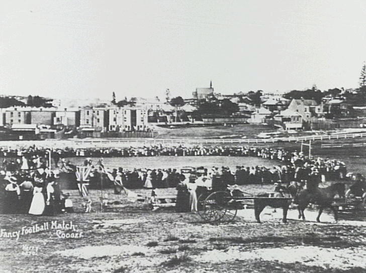 """St Nicolas Anglican Church Coogee from Coogee Oval at """"fancy football match"""": early 1900s."""