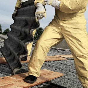 Removing asbestos roofing from property in yellow hazmat suit