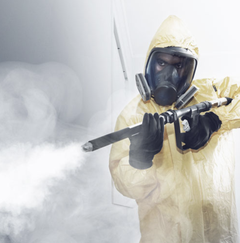 Man holding fogging gun performing meth decontamination