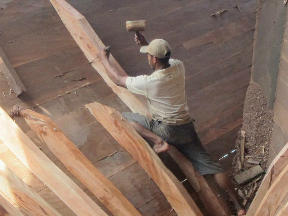 A Bugis craftsman works on the hull planks
