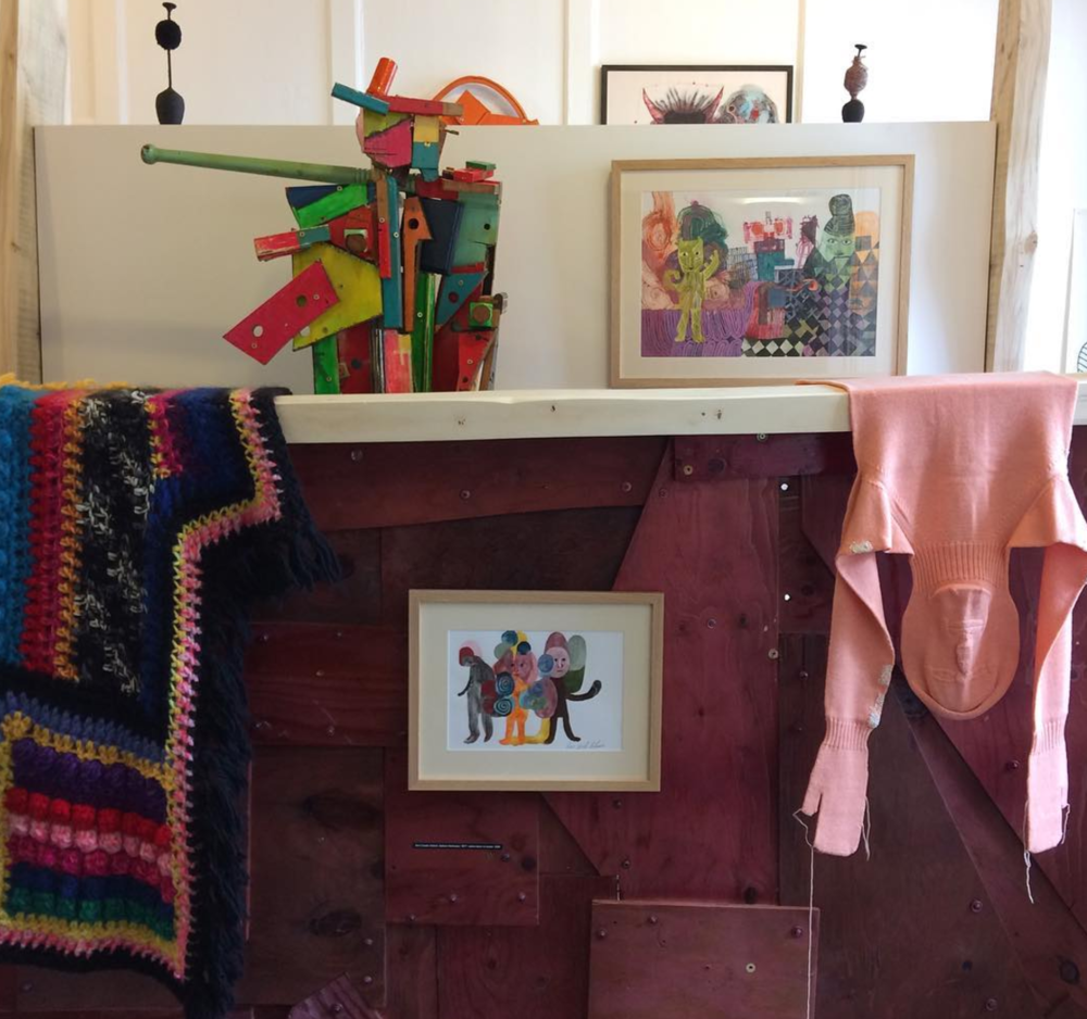 Paris Essex blanket here seen alongside watercolours by Ben Coode Adams, The Imperfect knitted body by Freddie Robins darned by Celia Pym and wooden sculpture by Clare Iles