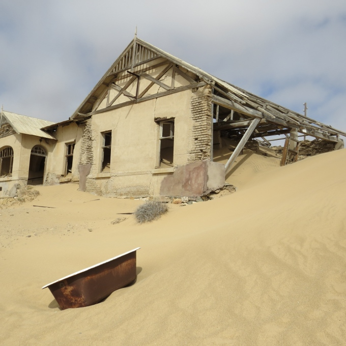 kolmanskop sand dune holding up a house namibia