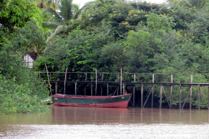 red boat docked on the essequibo