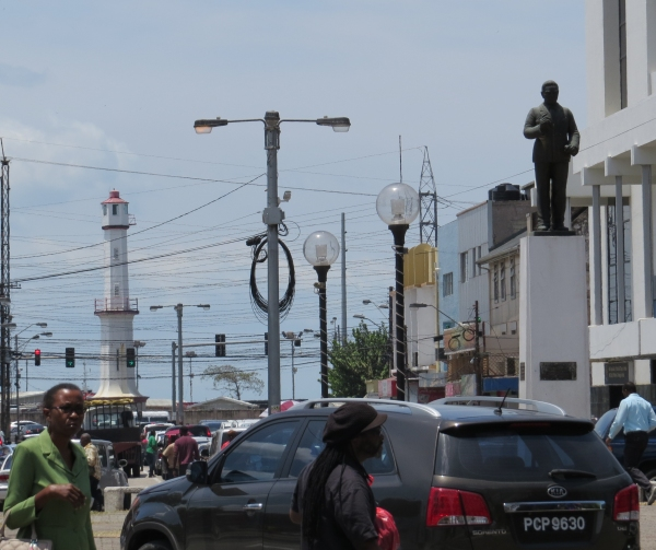 Bustling crowd on Frederick Street with Port of Spain Lighthouse and the statue of Arthur Cipriani, renowned Labor Leader, in the background.