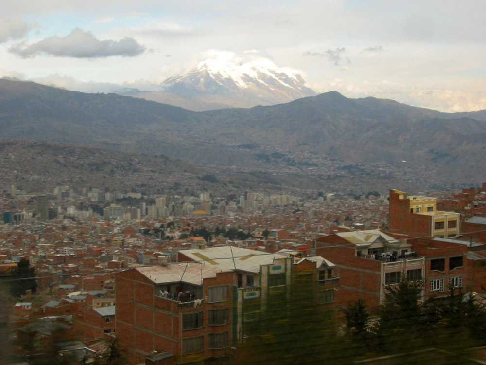 A view of la paz from a moving bus with Mount Illimani in the background.