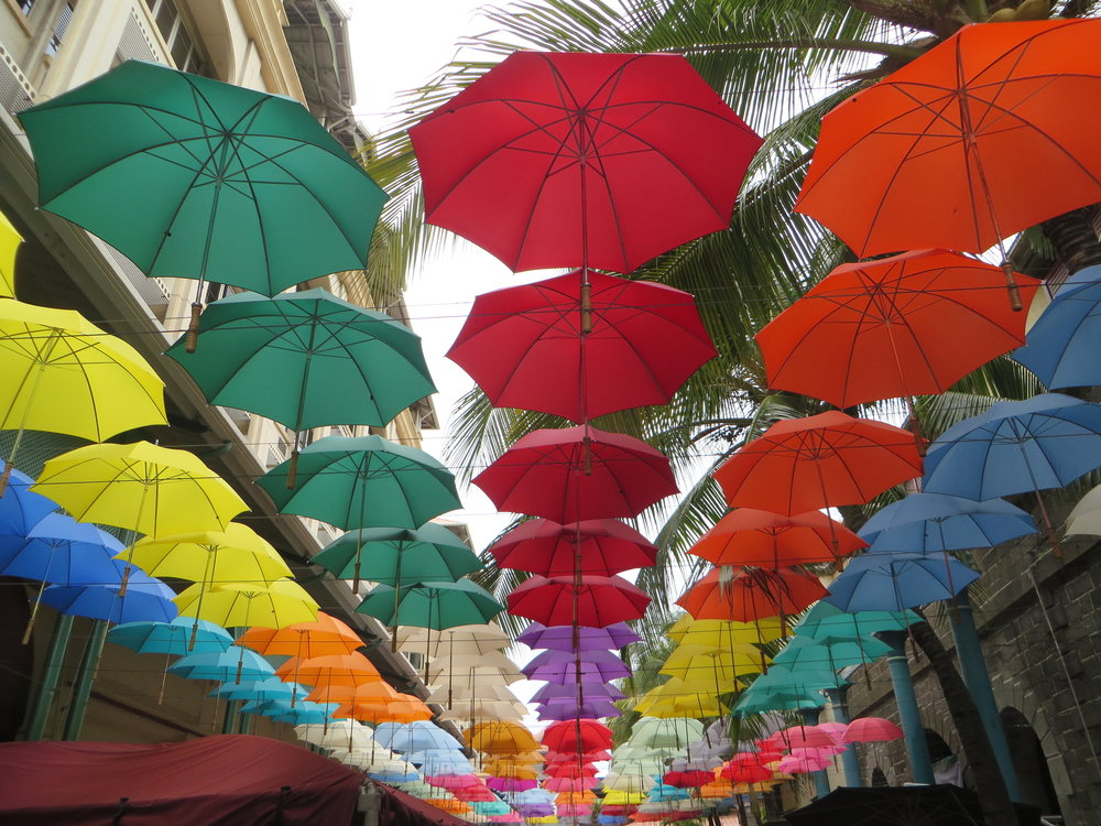 A rainbow of parasols hung above the waterfront walkway, providing both shade from the sun and a riot of color to pedestrians.