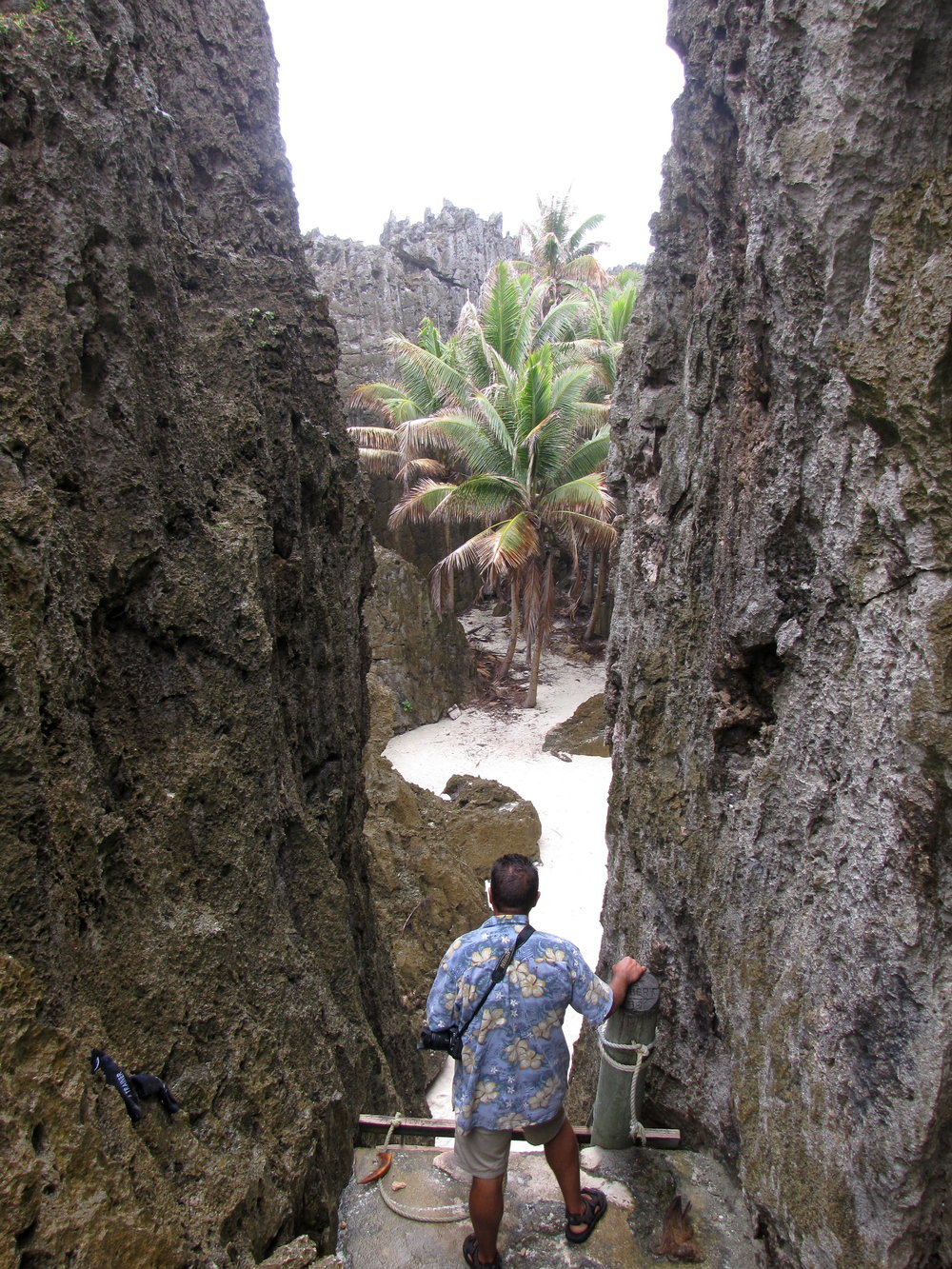 One of the most unique sites was the Togo (pronounced Tongo) Chasm. A narrow cleft in the limestone walls revealed an oasis complete with palm trees, white sand, but no water. We could, however hear the crashing OF the waves not far away. Above, Rob prepares to descend a very, very steep vertical ladder.