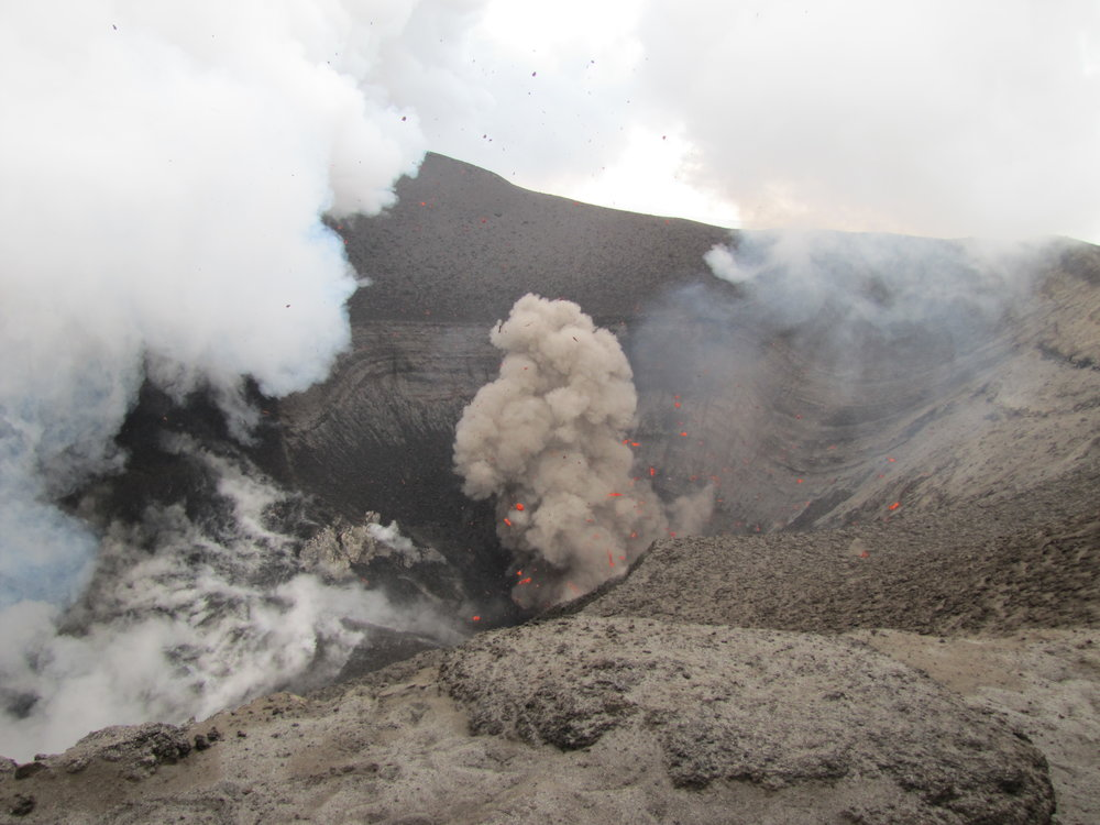 The volcano belched thick brown smoke,  heaps of steam and blue sulphurous vapor.