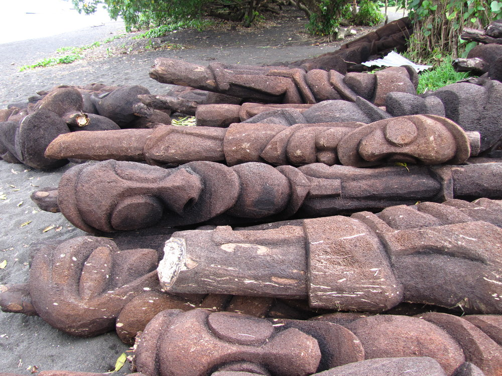 Carved tree ferns or black palms lie in a  heap on the beach getting ready for  transport to Vila and Noumea