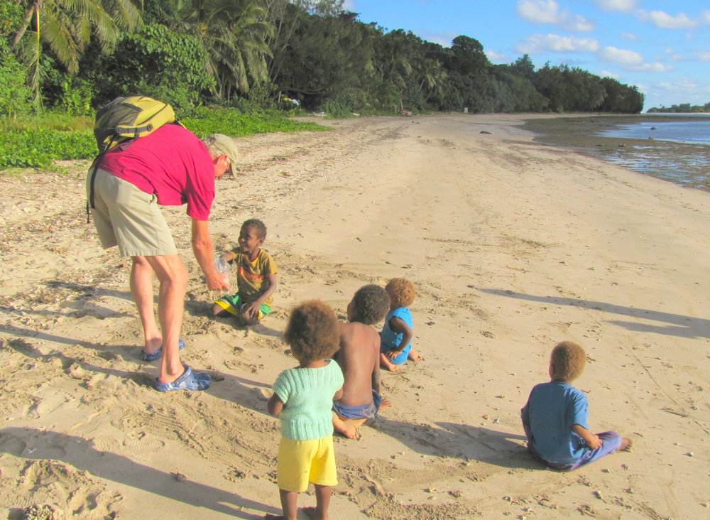 David shares peanuts on the beach with island kids.