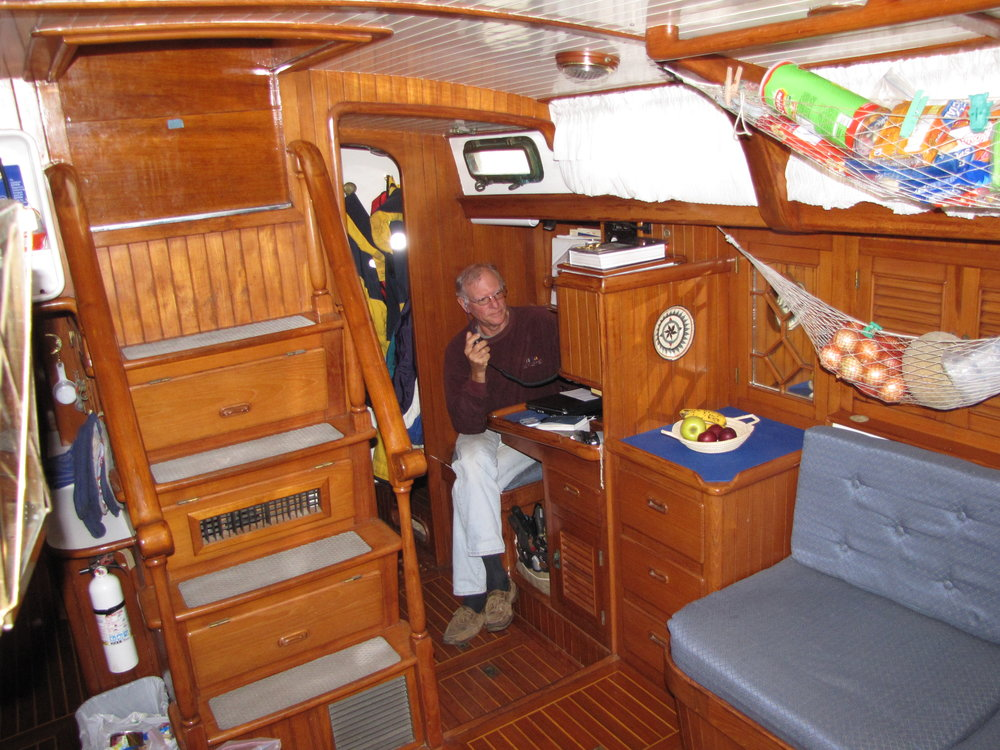 "An elegant teak ladder leads below decks into a well-appointed saloon. No need to duck ... there's plenty of headroom ... ~76"" worth."