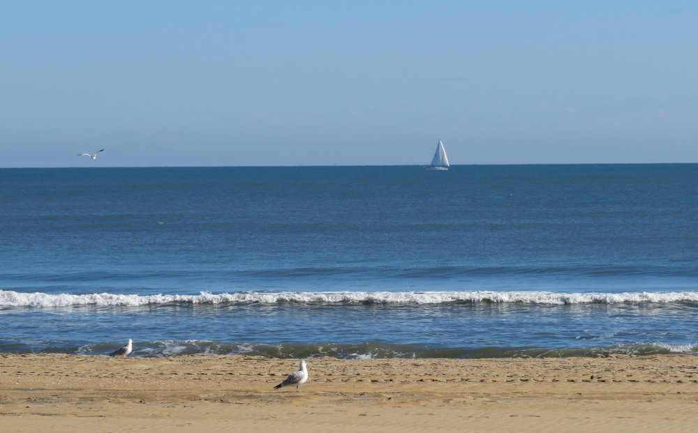 A lone sailboat skimmed along the horizon.