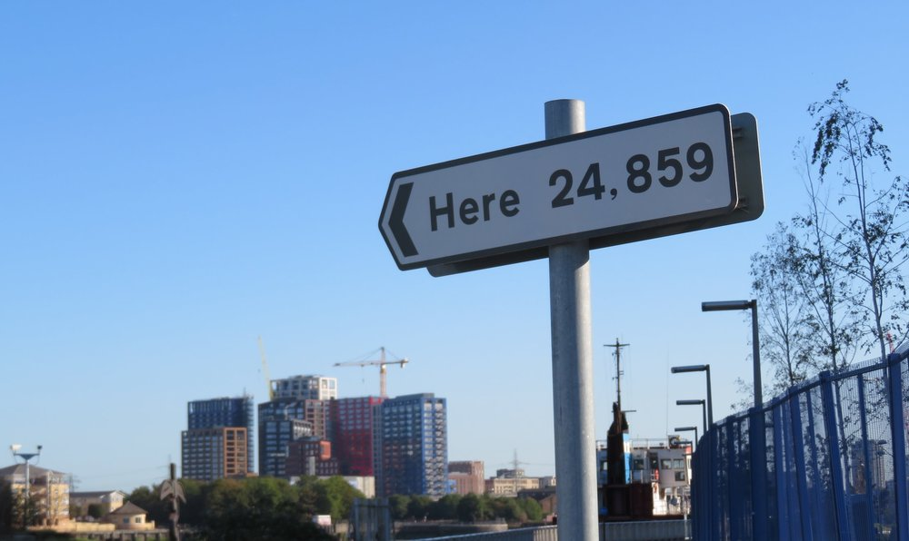 Or the nearby signpost 'Here', designating 24,859 miles from one end of the sign to the other … the long way around … the distance around the world.   (Signpost: Thomson & Craighead