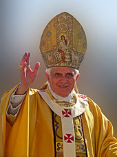 Pope Benedict XVI wears a pallium above, the white y-shaped vestment with red embroidered cross.