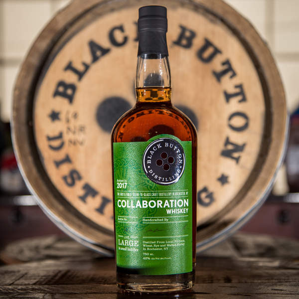 Black Button Distilling Collaboration Whiskey Bottle in front of Black Button Distilling Whiskey Barrel
