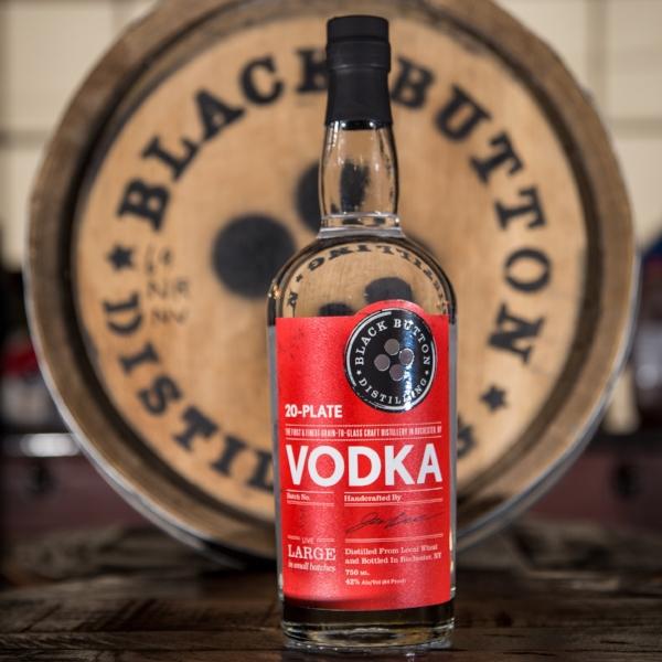 Black Button Distilling 20-plate vodka in front of Black Button Distilling barrel