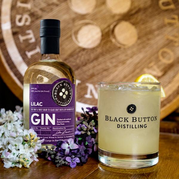 Award winning Black Button Distilling Lilac Gin bottle next to a lilac gin lemonade cocktail