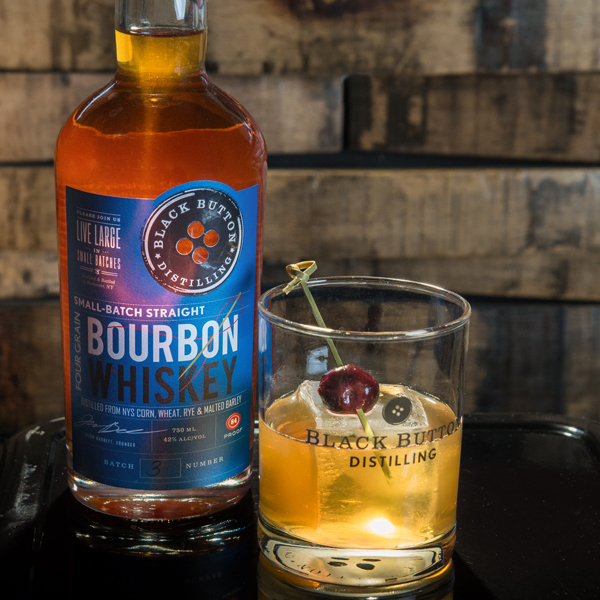 Black Button Distilling Small Batch Straight Bourbon Whiskey bottle next to Bourbon cocktail