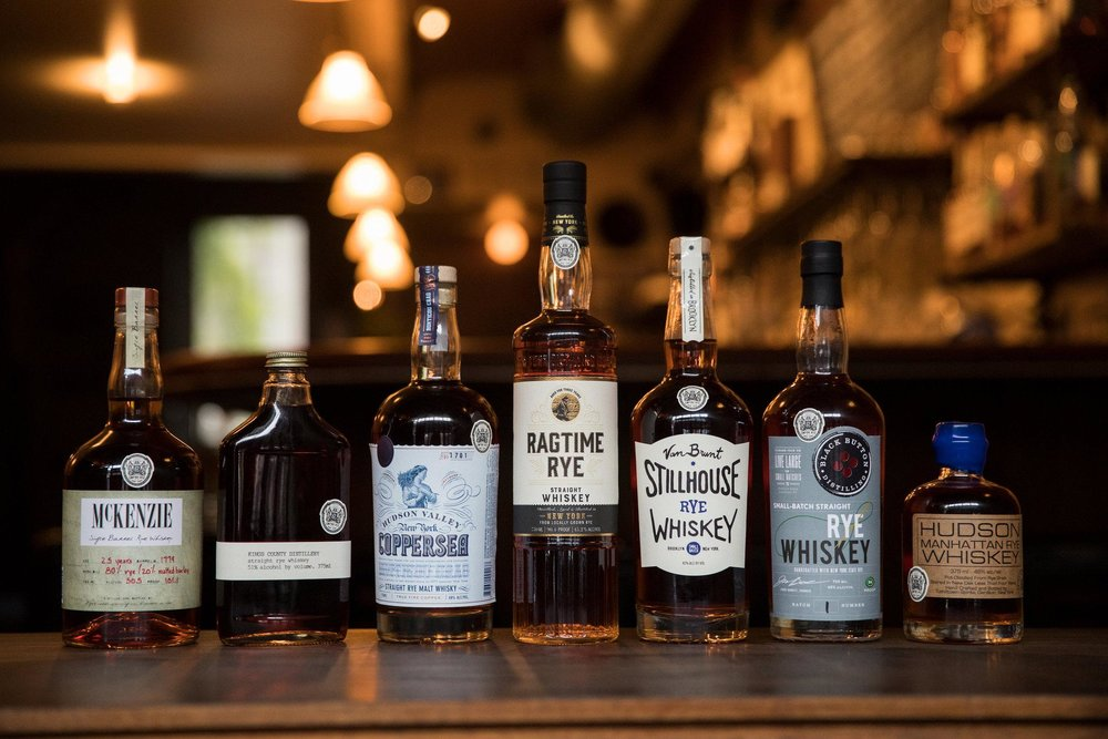 Bottles of whiskey bearing the round white Empire Rye logo, at Cardiff Giant, a bar in Brooklyn. Credit Benjamin Norman for The New York Times
