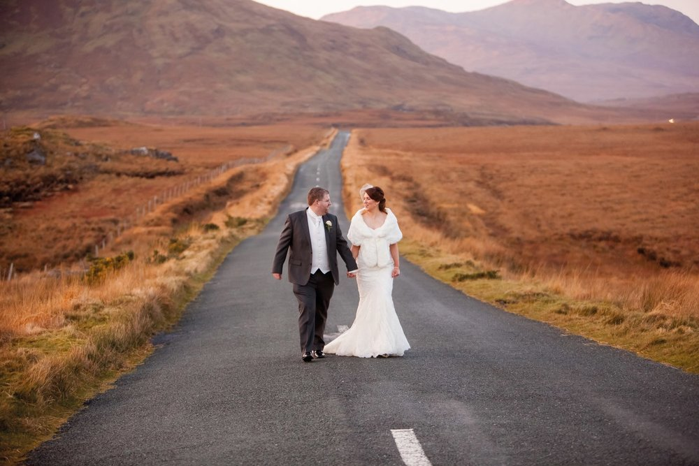 Ann-Marie Aspell and Tom O'Neill walking hand in hand along a winding Connemara road