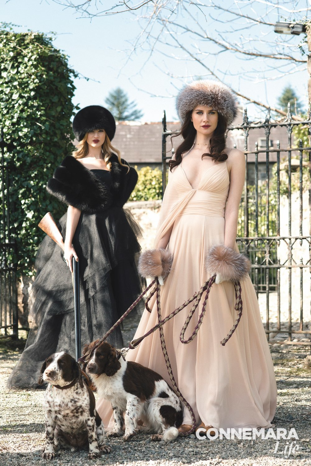 On Clara, left:  Christian Siriano gown, Resort 2015 collection; Surell Accessories fox fur stole and bubble hat in black by Surell Accessories   On Faye, right:  Christian Siriano blush silk chiffon pleated gown; gloves and fox fur cuffs and bubble hat in crystal by Surell Accessories; necklace available at Destin Jewelers