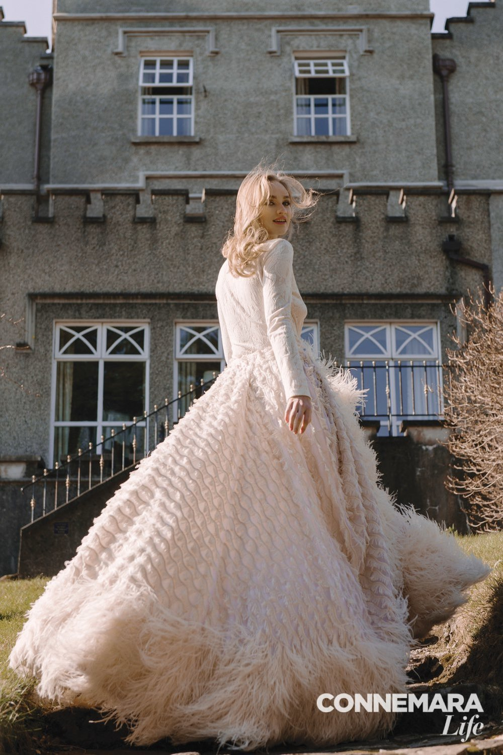 Sheer long-sleeve knit top and ivory feathered fringe ball gown by Christian Siriano