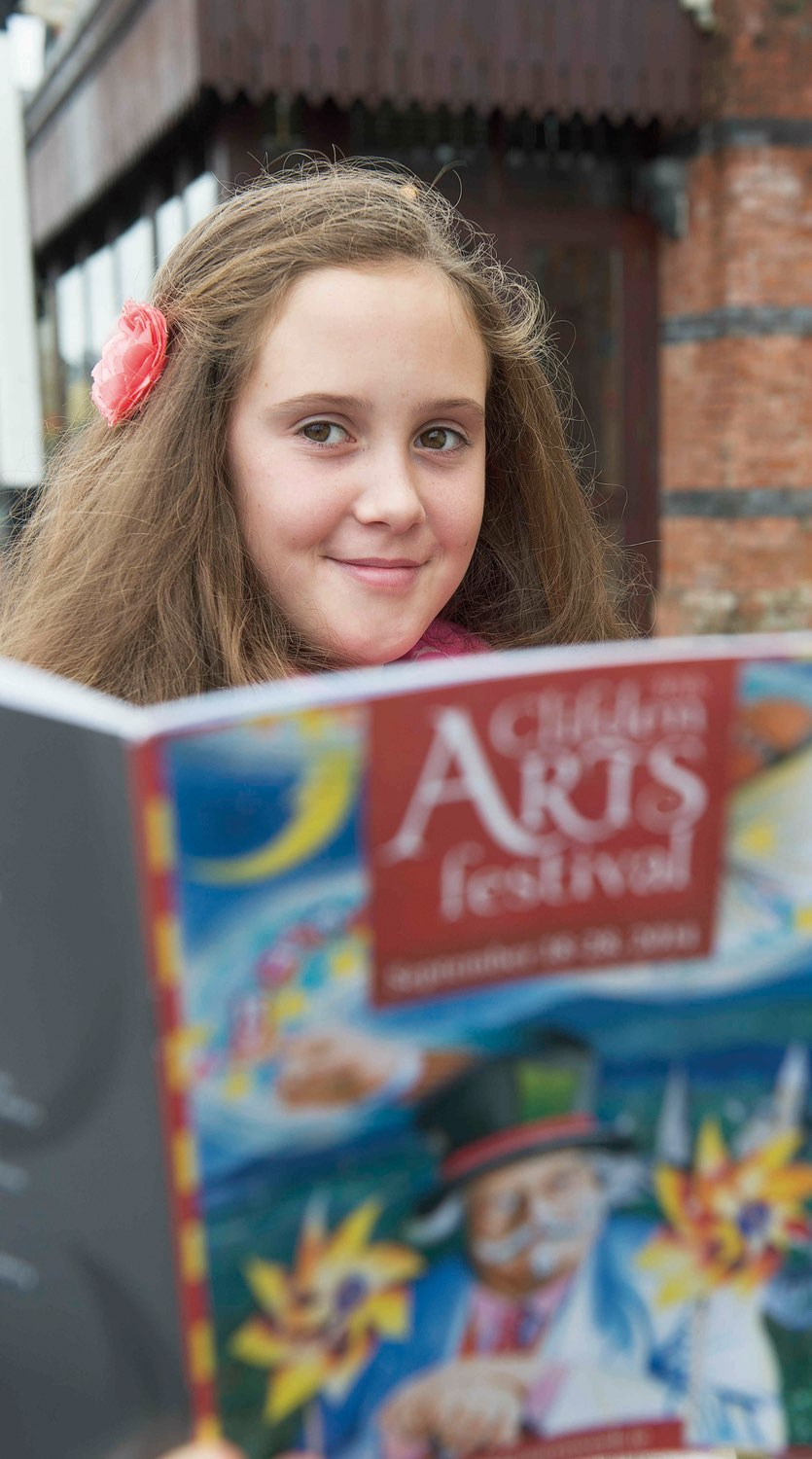 Student from Clifden Community School peers over Clifden Arts Festival booklet