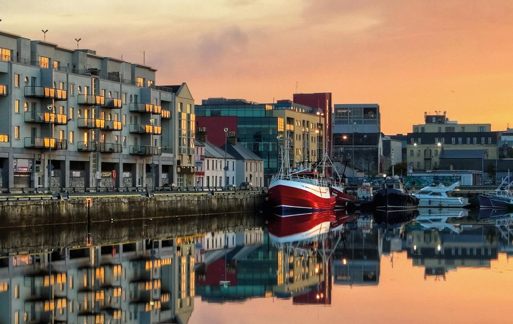 Morning view on the buildings and fishing boats along Galway Dock. Photo by Rihardzz / Shutterstock