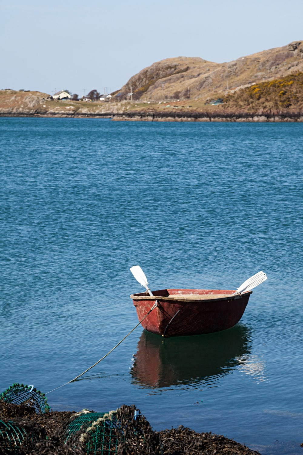 A row boat sits in the calm bay behind Rosroe.