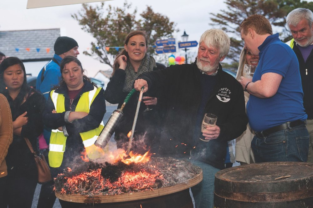 Group of festival goers standing around fire pit