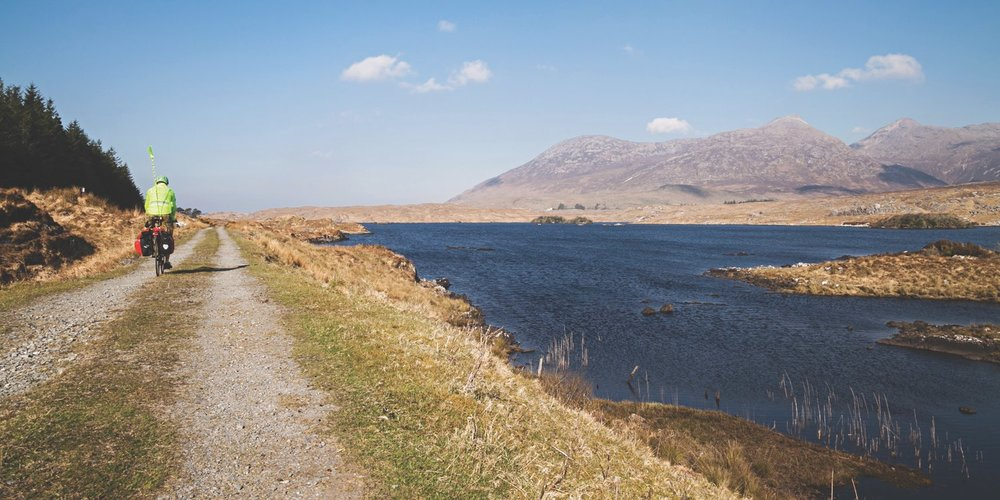 A cyclist follows the former railway line along the eastern shore of Derryclare Lough.