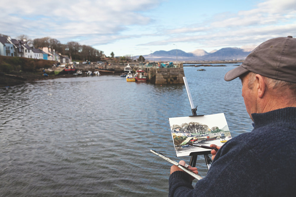 An artist at Roundstone painting the harbor with the Twelve Bens mountain range in the distance.
