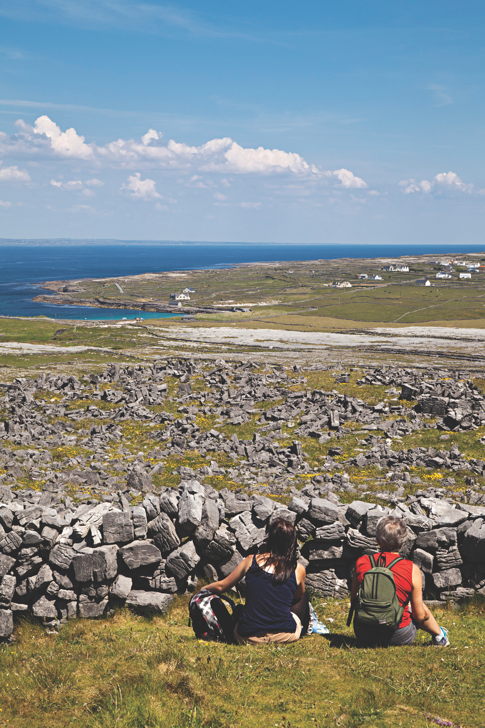 Hikers on the Aran Islands admire the view toward the Connemara coastline. Projects such as Middle Island and Galway Ghost Train aim to involve members of local communities as well as Aran Islanders.