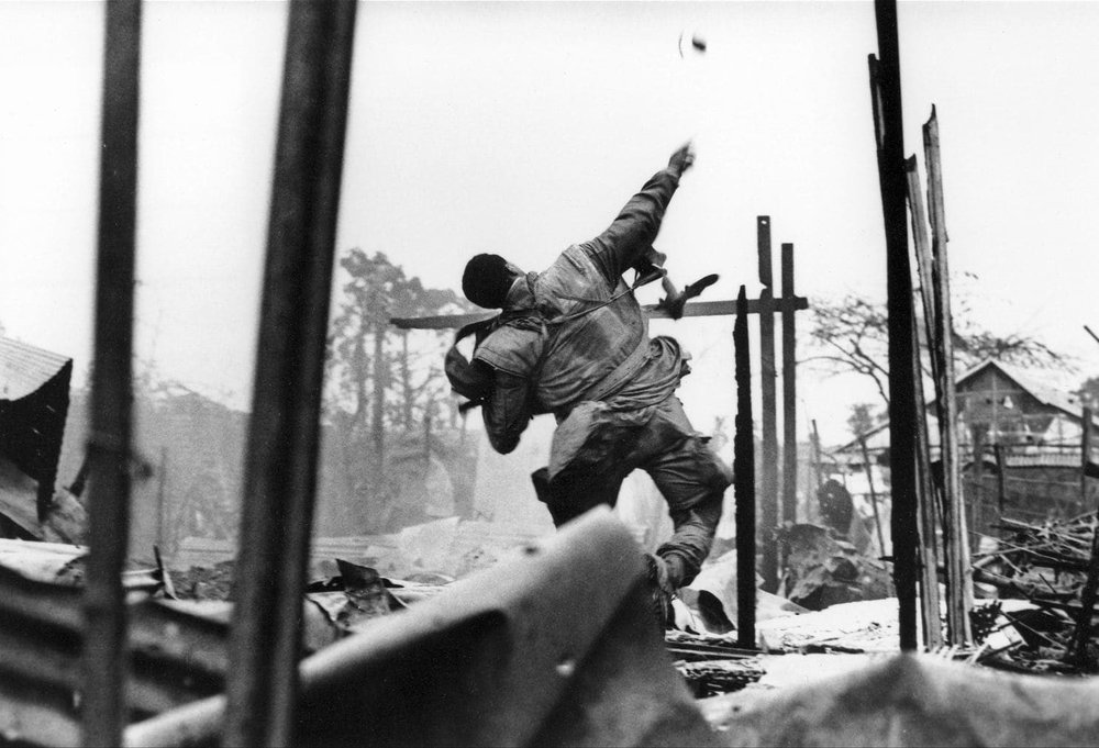 A U.S Marine Throws a grenade before being shot through his left hand.