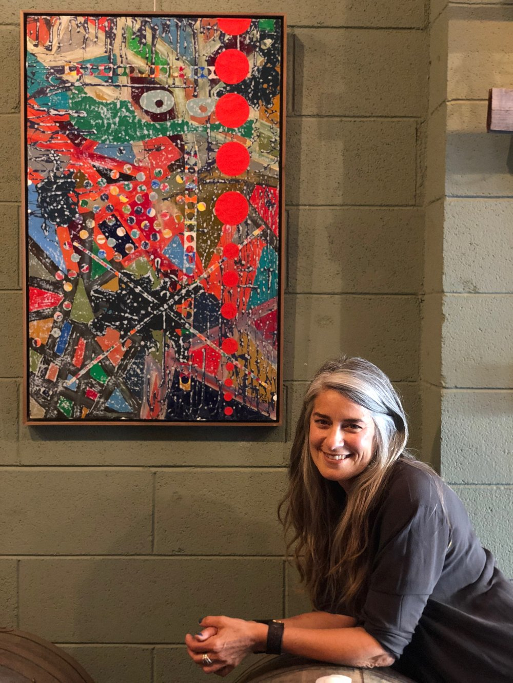Robin Fogelman with painting on display at Frogtown Brewery