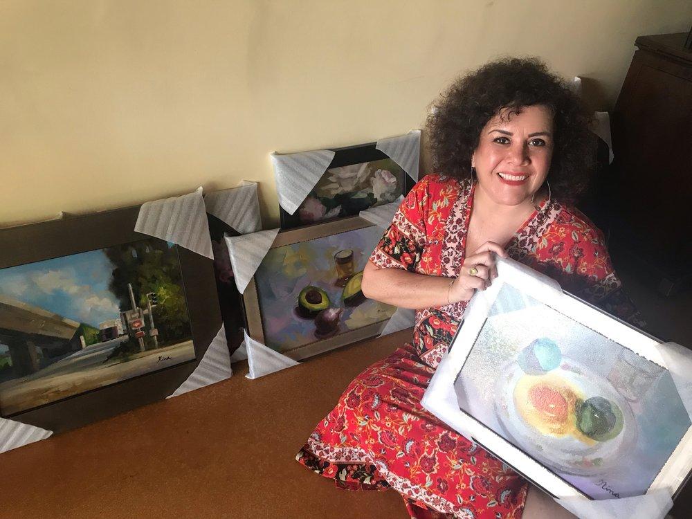 Nina Hoffmann posing with paintings