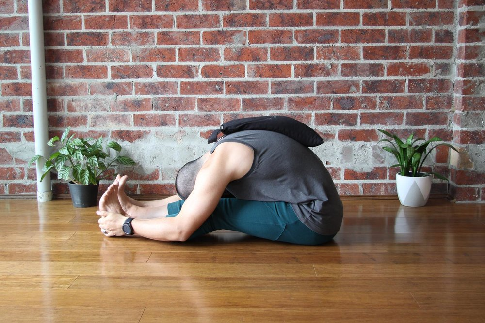 Paschimottanasana , with sandbag on spine