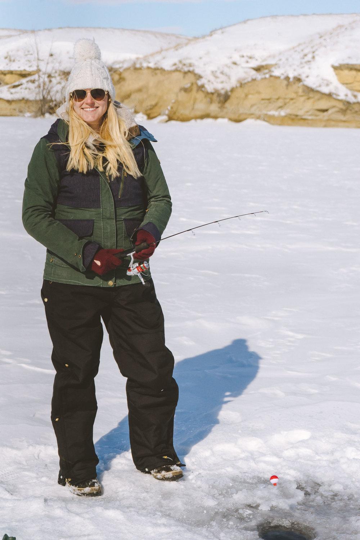 Adventure blogger Bri Sul ice fishing at Petrolia Lake near Winnett, Montana. Wearing Coach sunglasses, a Roxy coat, and the warmest Carhartt bibs.