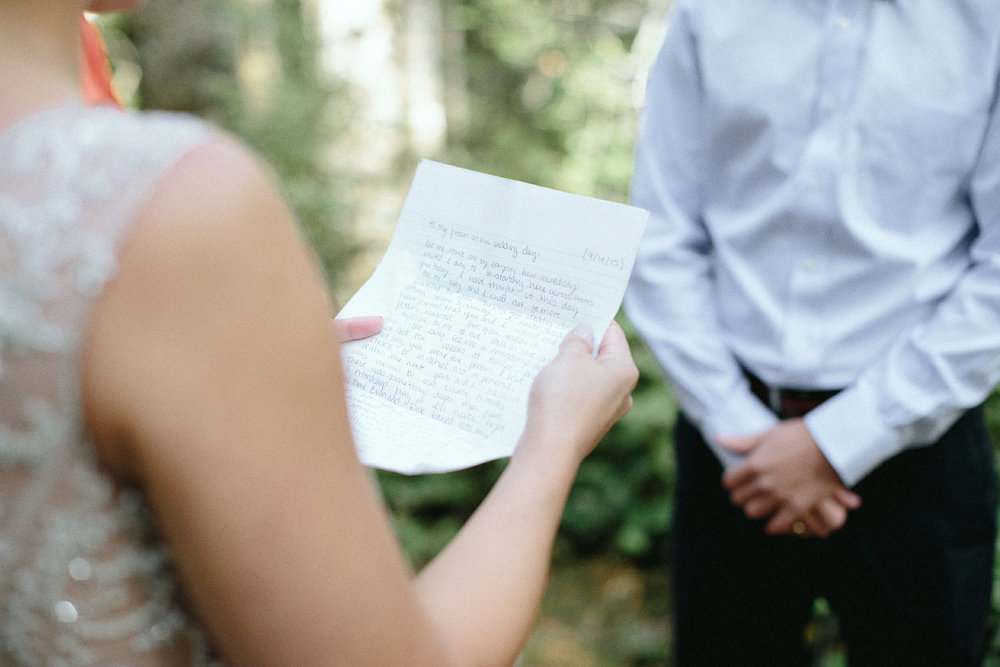 bride reading vows during an elopement in a forest cathedral on rattlesnake ridge