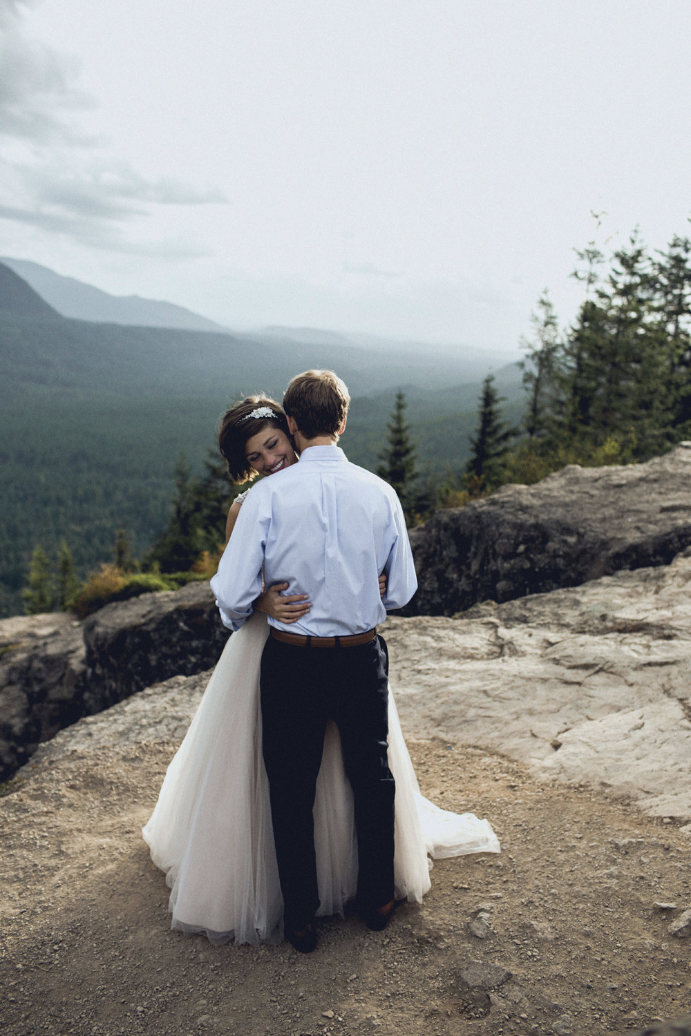 bride and groom post at the top of rattlesnake ridge after eloping