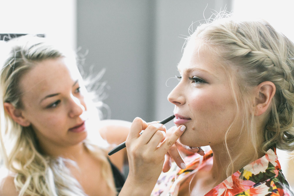 blonde bride getting her makup done before the wedding