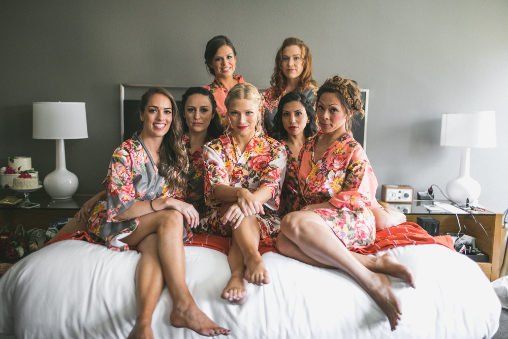 bride and her bridesmaids on the bed in their robes