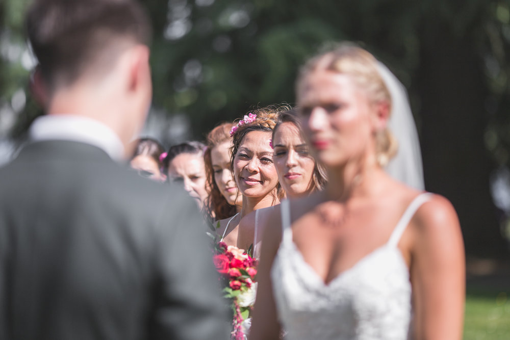 bridesmaids line up behind the bride at the alter in leschi park in seattle for a wedding