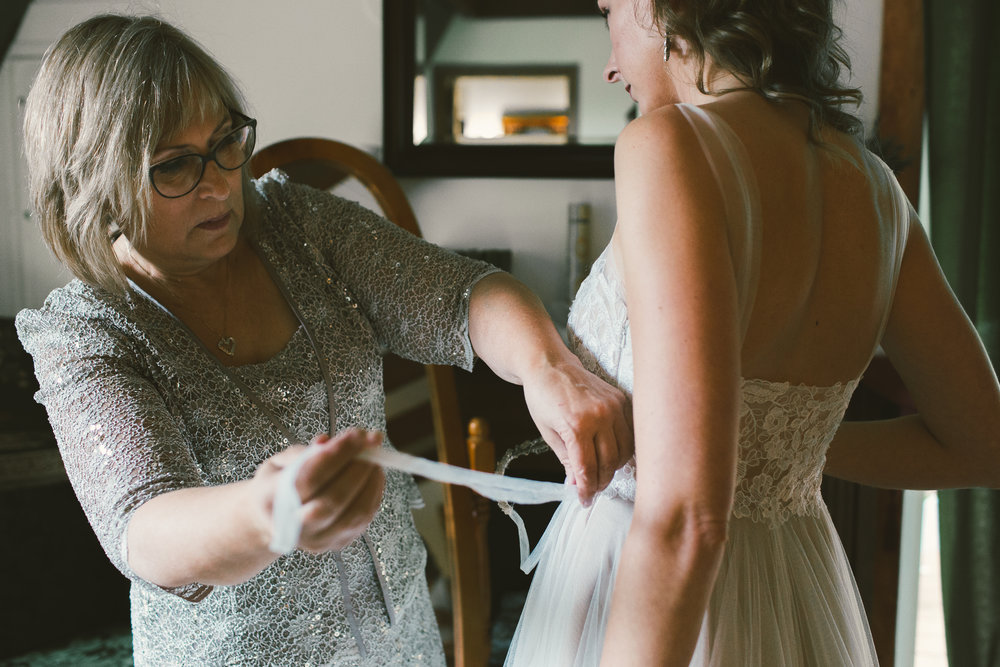 mother of the bride tying brides wedding dress