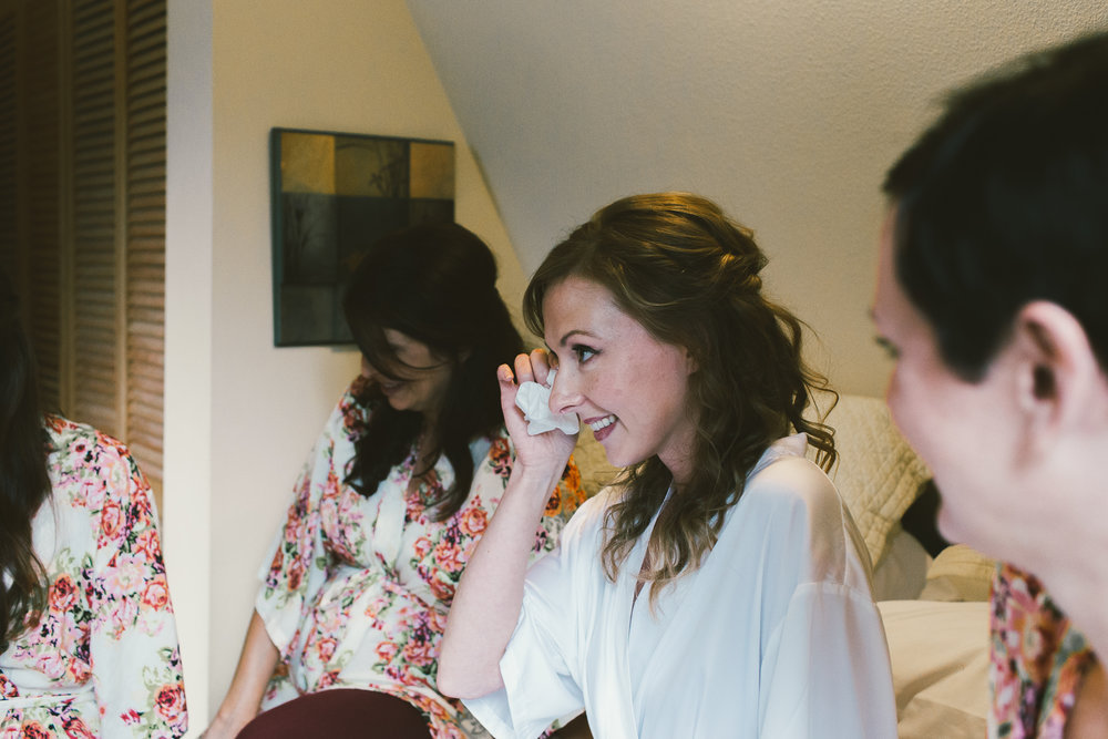 bride crying while talking to bridesmaids