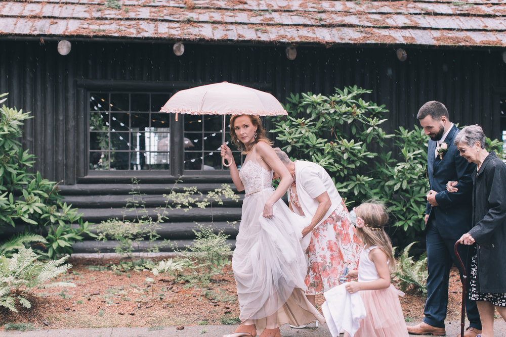 mother helping bride carry dress