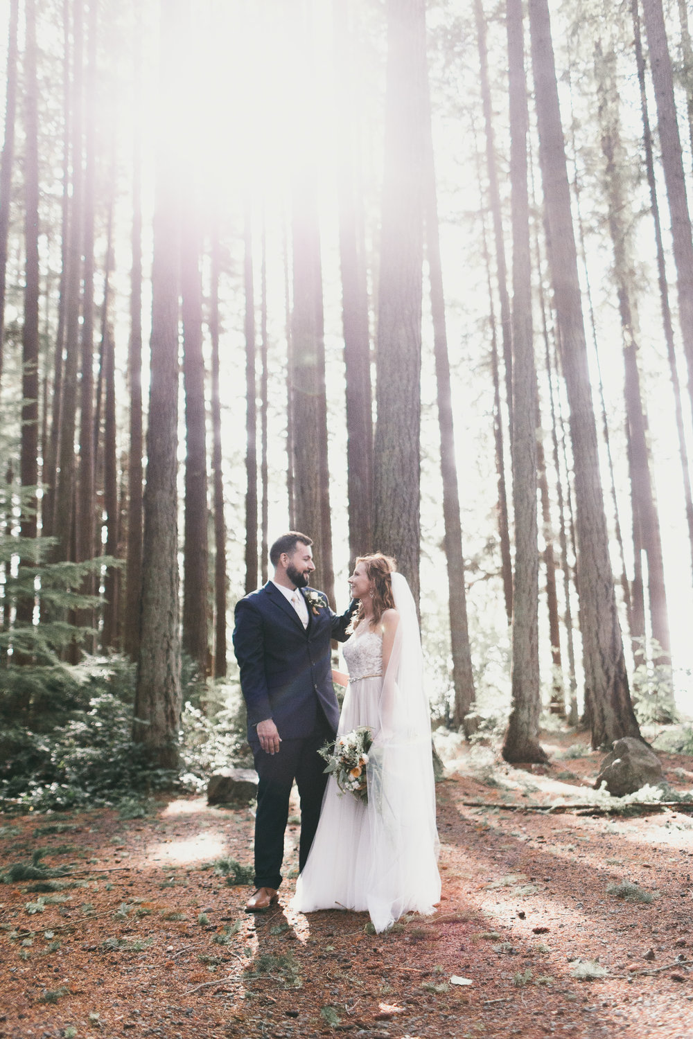 sun shining through trees at kitsap memorial state park with bride and groom
